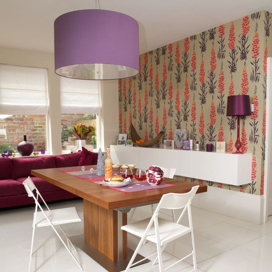 bold printed wallpaper feature wall sofa shelf table chairs and