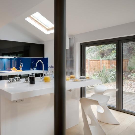 White Streamlined Kitchen With Blue Splashback