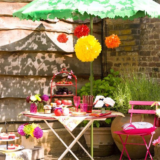 Small alfresco garden dining area with pink metal table and chairs in