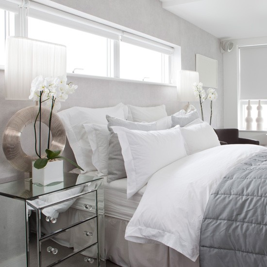 White and grey bed under a long window