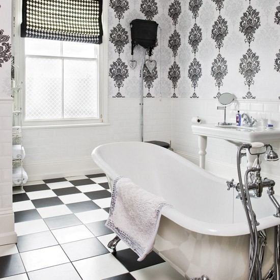 monochrome bathroom with tiled floors freestanding bath sink and