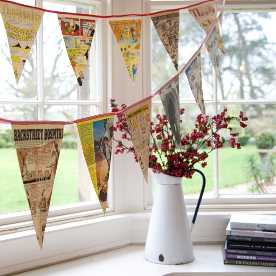 Bunting displayed in bay of window with jug of flowers.
