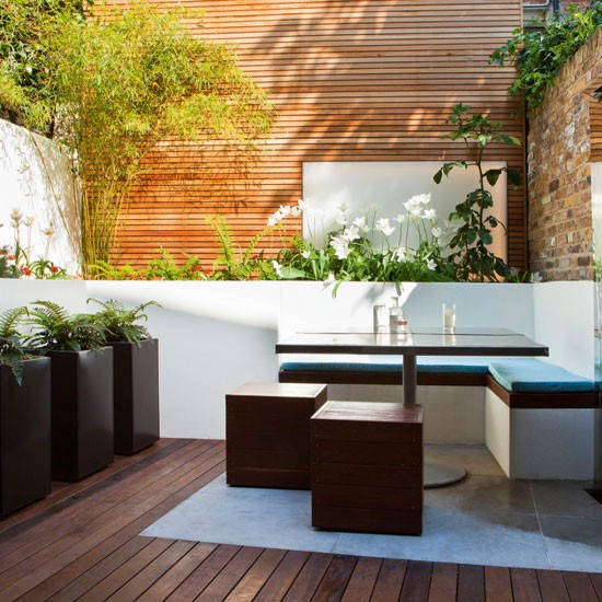 Decked garden with square table and black stools