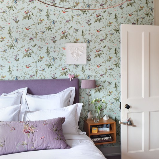 Bedroom with bird wallpaper and white and purple bed