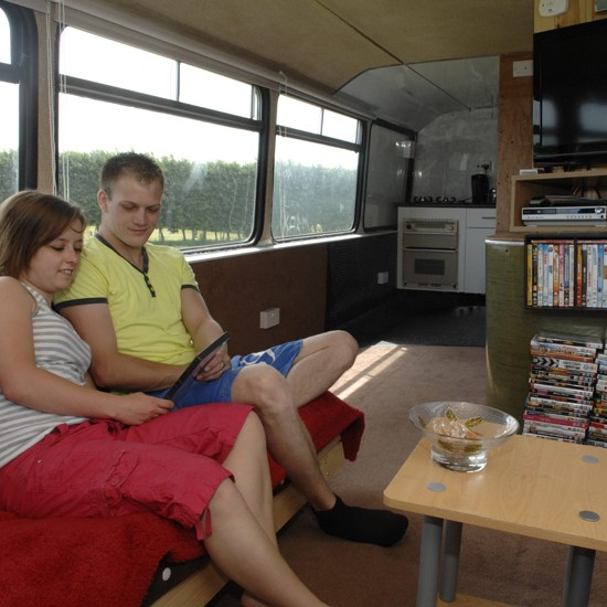 Daniel and Stacey relax in the TV lounge of their double-decker home (c) Chris Davey / SWNS.com