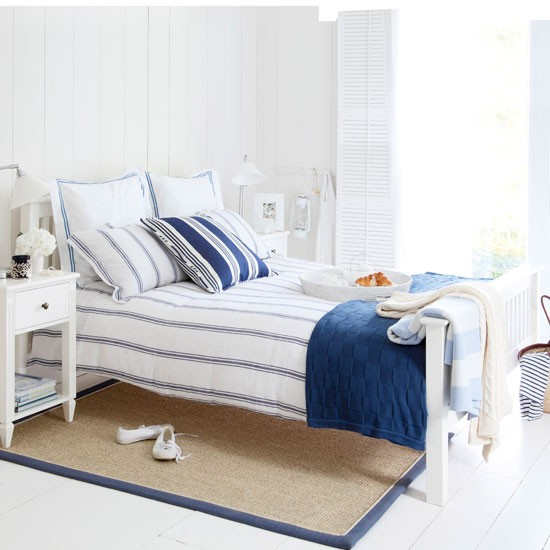Summer bedroom with nautical theme, wooden shutters and sisal bed