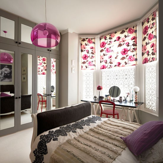 Summer bedroom with pink floral blinds, double bed and mirrored wardrobes