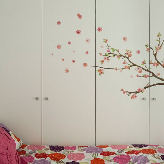 Summer bedroom with tree wall motif, and floral bed linen