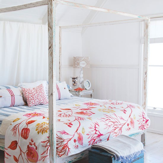 Summer bedroom with floral bedding and four-poster bed