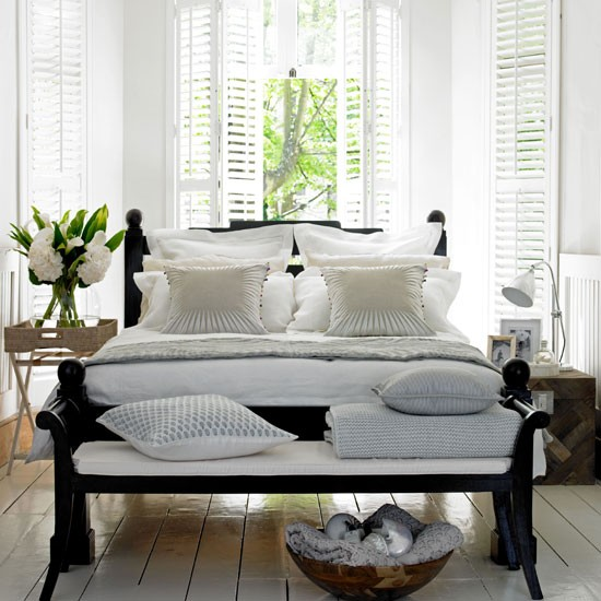 summer bedroom with colonial style dark wood bed with wooden shutters