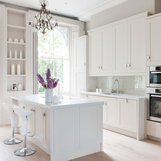 white kitchen with white cabinetry island unit and alcove shelving
