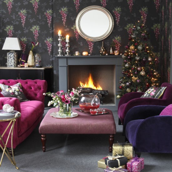 Christmas living room with black floral wallpaper, grey fireplace, purple chairs and pink footstool
