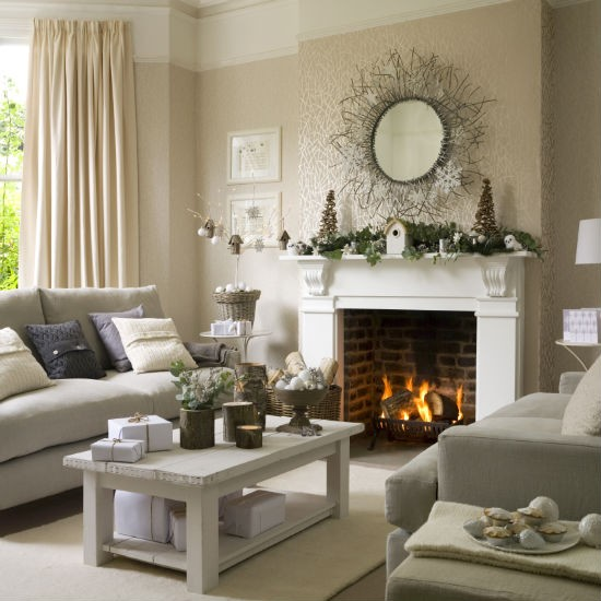 Christmas living room with neutral twig-patterned wallpaper, white stone fireplace decorated with garland, and neutral sofas