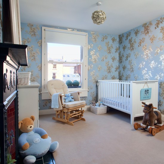 this pretty nursery is decorated with pale blue and gold wallpaper for