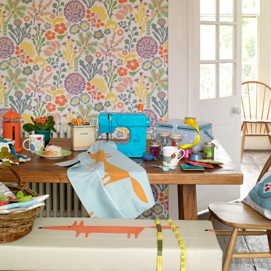 Colourful wallpaper behind table with blue sewing machine and tablewear