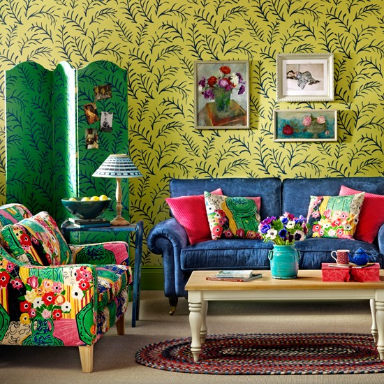 Blue sofa with colourful cushions and green printed wallpaper