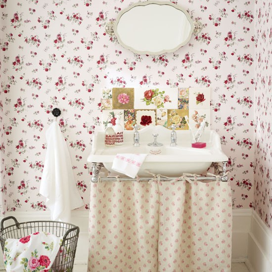 Bathroom sink with floral wallpaper and vintage mirror