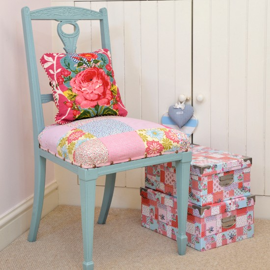 Blue chair with patchwork seat and cushion next to stacked boxes