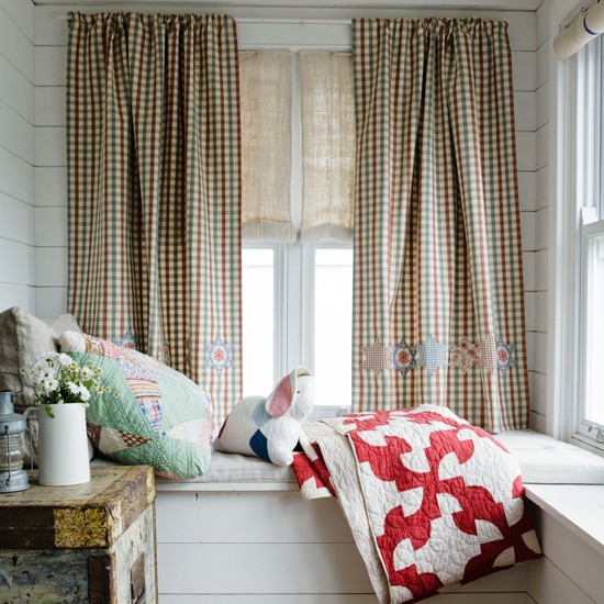 Window seat with patchwork pillow and throw and checked curtains