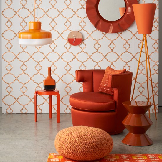 Orange chair and tables with patterned wallpaper