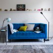 Modern living room with blue velvet sofa and task lighting