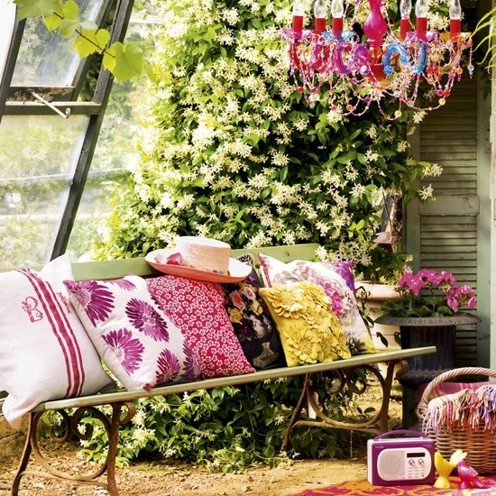 Summer garden with bench and bright cushions