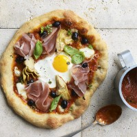 Artichoke, olive and Parma ham pizza with an egg on top