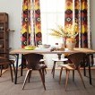 Dining room with wood furniture and colourful curtains