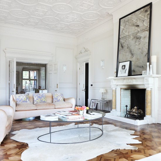 White open-plan living room with original fireplace, parquet flooring, metal coffee table and neutral sofa