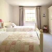Cream children's bedroom with patchwork throw