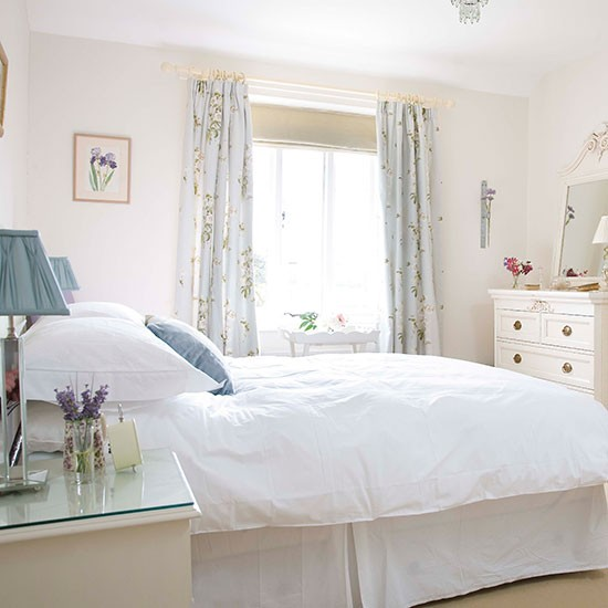white bedroom with pale blue floral curtains blue lampshade and white