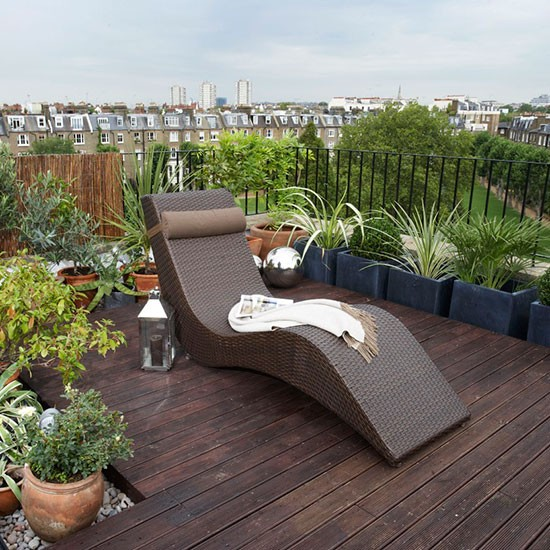 Small roof garden with wooden decking, potted plants and sun lounger