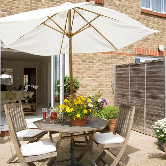 Small patio garden with wooden circular table and chairs and white parasol
