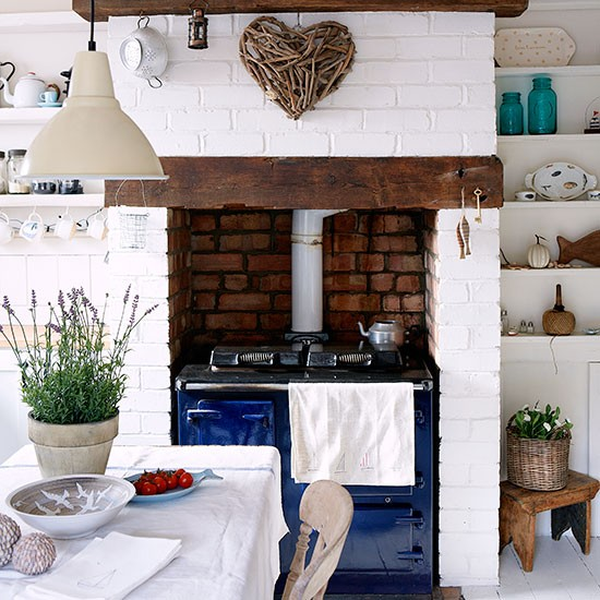 Country Kitchen With Brick Fireplace And Blue Aga