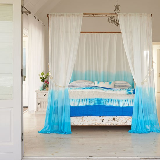 white bedroom with four poster bed and blue tie dye