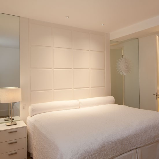 All white bedroom with panelled walls and white bedside table