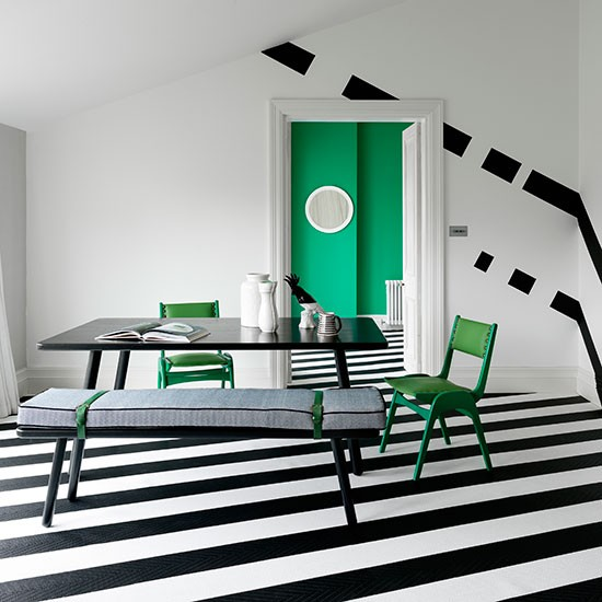 Black and white striped dining room with green chairs