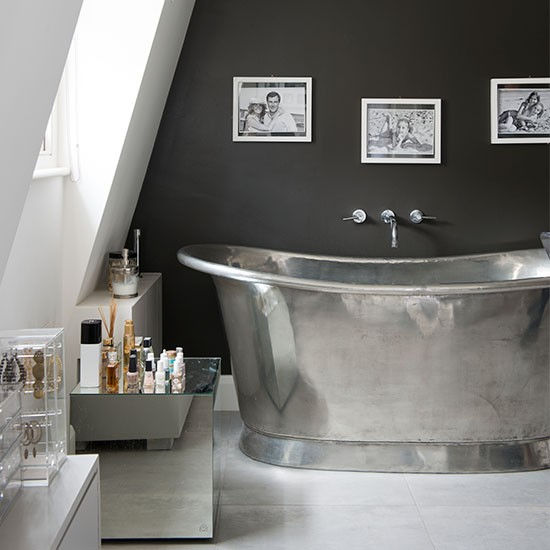 Streamlined attic bathroom with silver roll top bath for Luxury bathroom ideas uk
