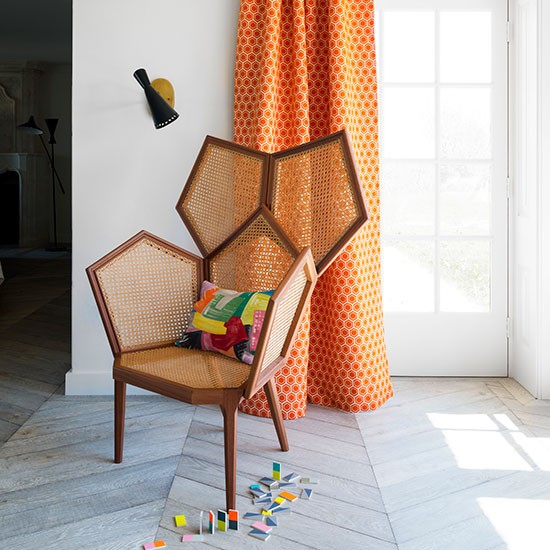 Living Room With Geometric Chair And Orange Curtain