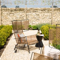 Walled garden with modern woven armchairs