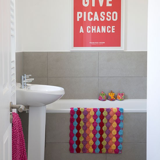 Grey bathroom with bright wall art and accessories for Bright coloured bathroom accessories