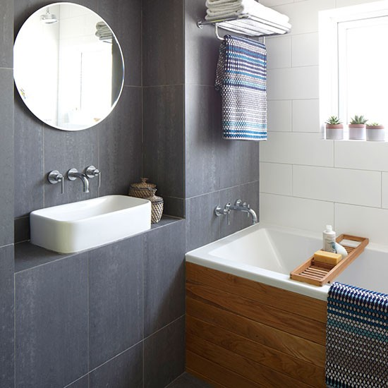 compact bathroom while large format grey tiles create a feature wall