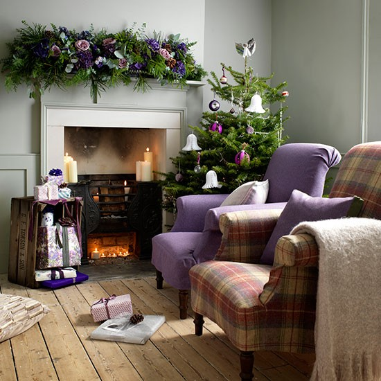 Country Christmas living room with natural wood flooring, fireplace, heather armchair and Christmas garland with purple flowers