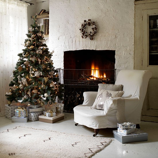Country Christmas living room with white brick walls, white flooring, white armchair and Christmas tree