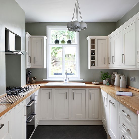 kitchen design White kitchen units contrast against green blue walls