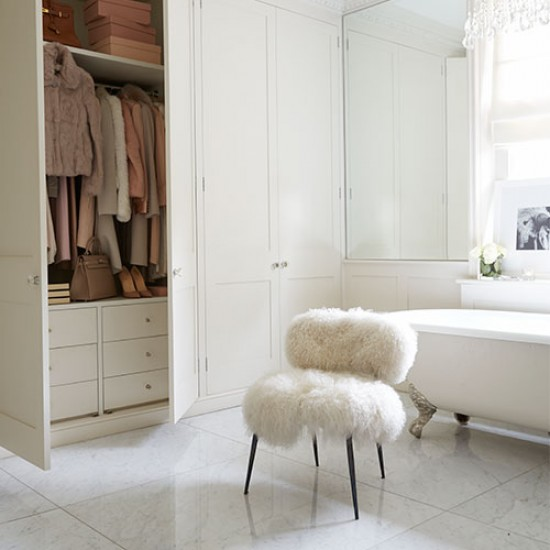 White marble-floored bathroom with statement chair  Modern bathroom design i...