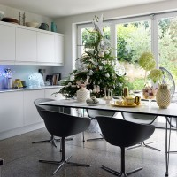 White dining room with concrete flooring