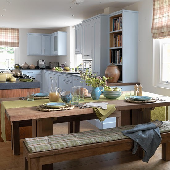open plan kitchen with pale blue units teak table and green table