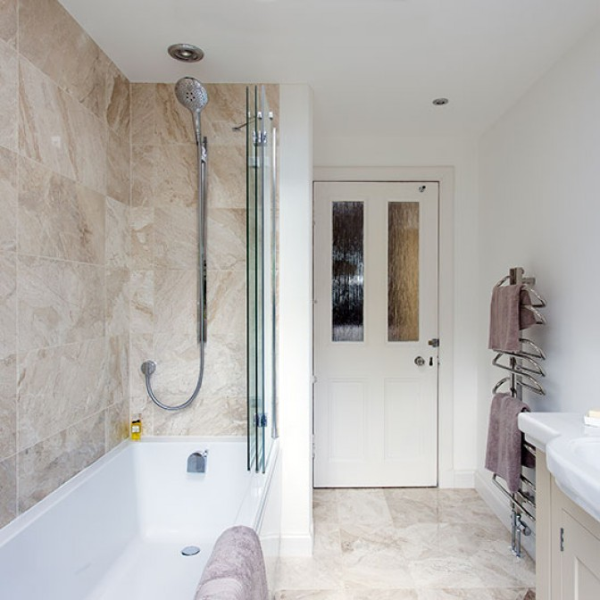 Marble bathroom with shower over bath