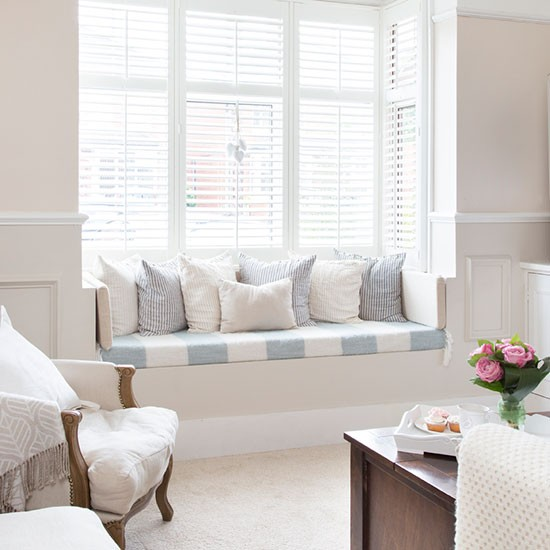 has a window seat covered in pale blue and white striped linen fabric